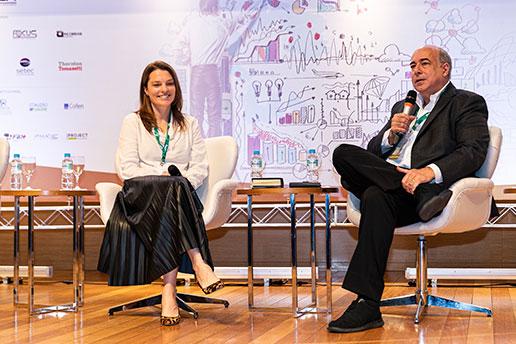 Registro de dois convidados, sentados e enquanto falam, durante o Simpósio Internacional.