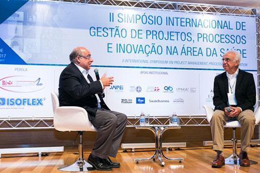 Registro de dois convidados, sentados e enquanto falam, durante o II Simpósio Internacional.