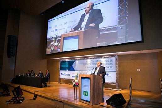 Simpósio Internacional, registro de um convidado enquanto ministra uma palestra com um telão no fundo.