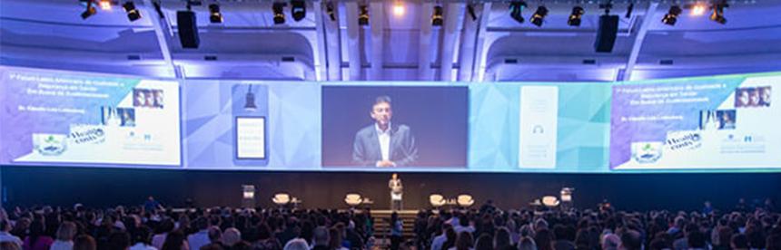 Registro de um evento onde o Dr. Claudio Lottenberg, Presidente do Conselho da Sociedade Beneficente Israelita Brasileira Albert Einstein, aparece em uma tela enquanto ministra uma palestra.