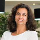 Dra. Helena Hachul de Campos em pé e sorrindo. Foto de perfil.